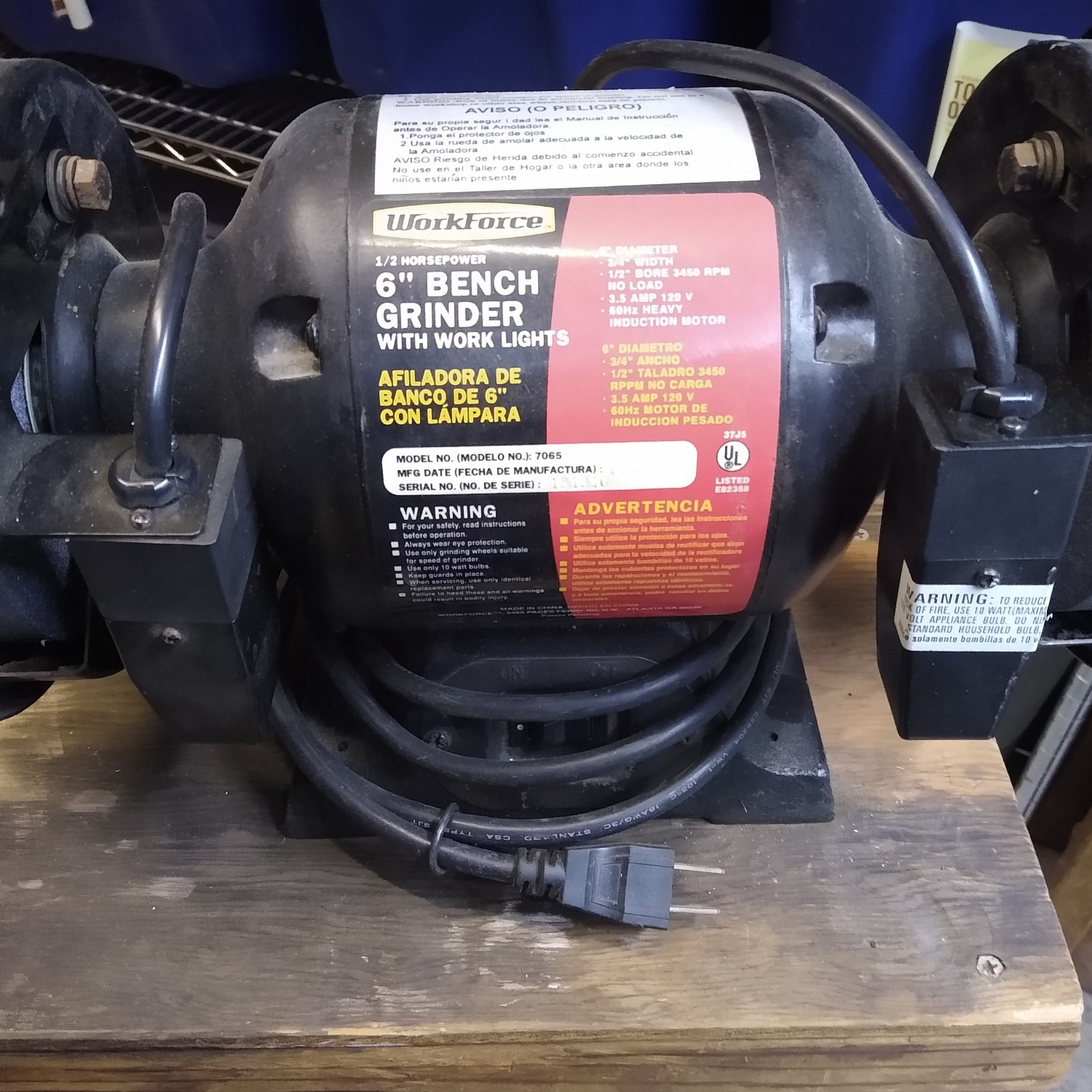 Bench grinder mounted on small table.